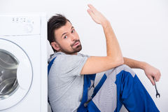 Washing. Sad young man in uniform is sitting near the washing machine, isolated on white background Stock Images