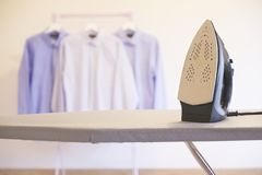 Washing shirts hanging up to dry and iron board indoor wooden interior royalty free stock images