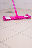 Washing of tile floors by pink mop Royalty Free Stock Photography