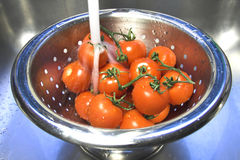 Washing tomatoes. Red tomatoes in a colander under running water Royalty Free Stock Images