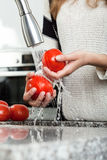 Washing tomatoes under the tap Royalty Free Stock Photography