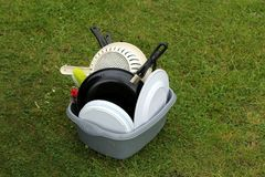 Washing up bowl with dirty pots and plates, on the grass at a ca Royalty Free Stock Photo