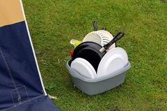 Washing up bowl with dirty pots and plates, on the grass outside Royalty Free Stock Photography