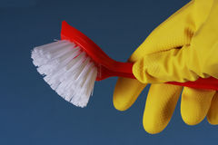 Washing Up Detail. Closeup of a yellow rubber glove holding a red washing up brush against a blue background Stock Photography