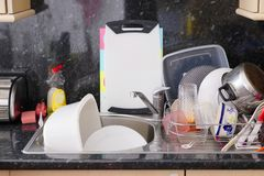 Washing up sink drainer dishes plates cutlery pots pans messy kitchen untidy stock images