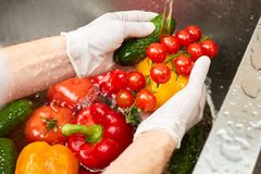 Washing vegetablea in a sink. Water flowing on vegetables in a sink royalty free stock image