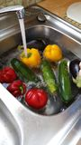 Washing vegetables in kitchen sink Stock Image