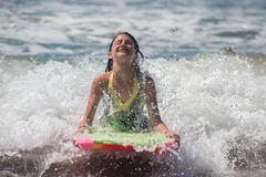 Washing in with the white water. Girl child feeling the ocean surge as she rides the boogie board Royalty Free Stock Photography
