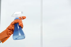 Washing Window. Spraying window cleaner on the glass with a spray bottle and gloves Royalty Free Stock Photo