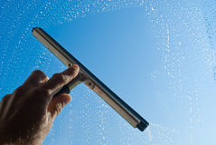 Cleaning the window with a squeegee. Washing and cleaning the window with professionnal squeegee Stock Photo