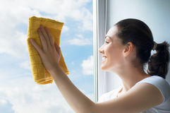 Washing windows. A young woman washing windows Royalty Free Stock Photos