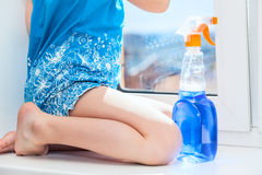 Washing windows in house, legs of unrecognizable girl Royalty Free Stock Photos