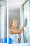 Washing windows. Pretty, young woman doing house work - washing windows stock photo