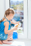 Washing windows with rag and spray, small girl in blue dress Stock Photos
