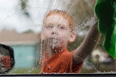 Washing Windows. The view of a little boy washing a car window as seen from the other side of the window Stock Images