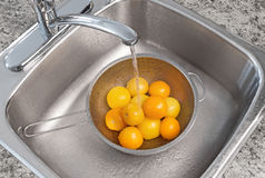 Washing yellow tomatoes Royalty Free Stock Image
