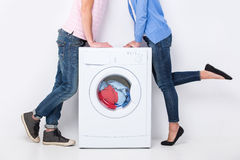 Washing. Young beautiful couple with a washing machine, on the white background Royalty Free Stock Photos