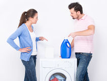 Washing. Young couple with detergent near the washing machine on white background Stock Photo