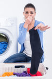 Washing. Young woman near the washing machine is keeping smelly sock Stock Images