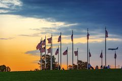 Sunset over waving american flags with tourists and an airplane landing. Washington D.C., USA, october 2016: sunset over waving american flags with tourists and royalty free stock photos