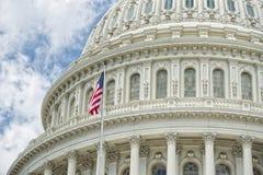 Washington DC Capitol detail on cloudy sky. Washington DC Capitol dome detail with waving american flag Stock Photo
