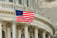 Washington DC Capitol detail on cloudy sky. Washington DC Capitol dome detail with waving american flag Royalty Free Stock Photography