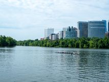 Rowers practice on the Potomac River with office buildings in Arlington, VA in background stock image