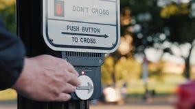 Washington DC, los E.E.U.U., octubre de 2017: Una mano del ` s del hombre presiona un botón en un semáforo para cruzar el camino almacen de metraje de vídeo