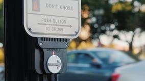 Washington DC, los E.E.U.U., octubre de 2017: Una mujer presiona un botón en un semáforo para cruzar el camino almacen de video