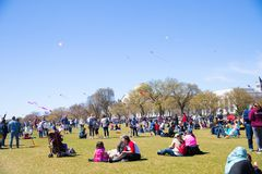 A large crowd of adults and children flying kites at the Kite Festival on the National Mall. WASHINGTON, DC - March 31, 2018: A large crowd of adults and Royalty Free Stock Photos