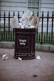 Washington DC: Overflowing trash can on the sidewalk of downtown DC. Concept for garbage, clean up, enviornment,. Overflowing trash can on the sidewalk of royalty free stock image