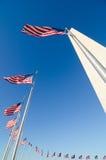 Washington DC, Washington Monument e bandiere degli Stati Uniti in un chiaro cielo Immagine Stock