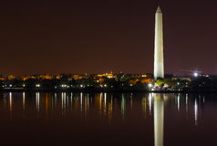 Washington Monument at night with city skyline on background. Colorful reflections in water of Tidal Basin Royalty Free Stock Image