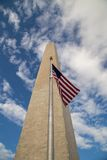 Washington Monument soaring with US Flag. From the base of  the recently reopened 290 foot Washington memorial a US Flag waves against the soaring monument into Royalty Free Stock Photos