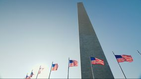 Washington Monument against the blue sky. The Washington Monument, a sunny flare from the flag that flutters in the wind. 4K video stock video footage