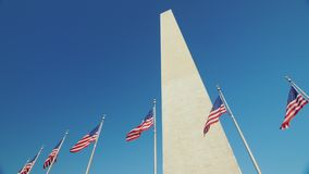 Washington Monument in the background of a clear blue sky. The Washington Monument, a sunny flare from the flag that flutters in the wind. 4K video stock video footage