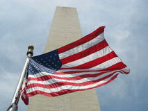 Washington Monument with the USA flag. Waving in the wind Royalty Free Stock Photography
