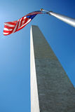 Washington Monument in Washington DC. View of the Washington Monument in Washington DC with waving flag and beautiful blue sky in background Stock Photo