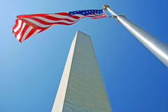 Washington Monument in Washington DC. With flapping american flag on a flagpole Royalty Free Stock Image