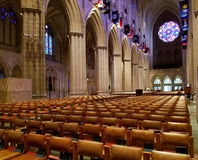 Washington National Cathedral interior view. View of the famous West Rose window. Gothic Cathedral interior with arches lining the Nave, framing removable seats Stock Photo