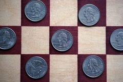 Quarters on the chessboard. `Washington Quarter` - quarter dollar. United States Mint`s 50 State Quarters Program Royalty Free Stock Photos