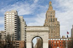 Washington Square Park Arch in New York City. Washington Square Park Arch and historic buildings with an American flag on a clear winter day in Manhattan, New Stock Photo