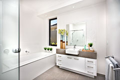Washroom with a bath tub beside a window and tap. The room isdecorated nicely with green plants on vase beside the basin and tap near  the counter cupboard Royalty Free Stock Photography