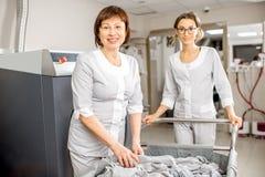 Washwoman supérieur avec l'assistant dans la blanchisserie images stock