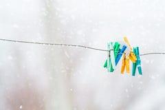 Wasknijpers op de aluminiumdraad in de natte sneeuw Royalty-vrije Stock Afbeelding