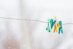 Wasknijpers op de aluminiumdraad in de natte sneeuw, close-up Royalty-vrije Stock Foto's