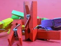 Wasknijpers van verschillende kleuren op haarden roze als achtergrond op bovenkant Stock Fotografie