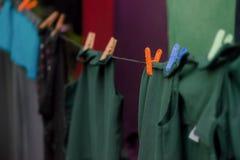 Waslijn met schone donkere kleren die het milieuvriendelijke in openlucht hangen drogen Stock Afbeeldingen