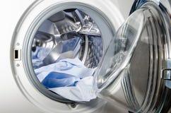 Wasmachine met blauw overhemd wordt geladen dat Stock Foto