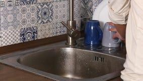 Wasschotel door mensenhanden met lopend water van kraan in keuken stock video